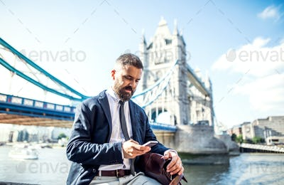 Hipster businessman with smartphone sitting by the Tower Bridge in London.
