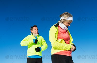 Senior couple runners resting in winter nature. Copy space.