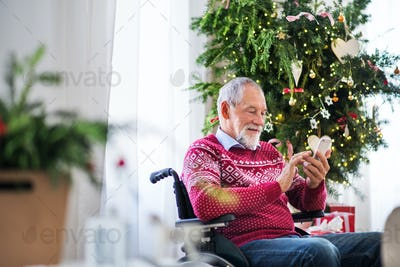 A senior man in wheelchair with mobile phone at home at Christmas time, texting.