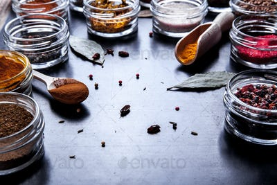 Spices on black background in special jars. Food