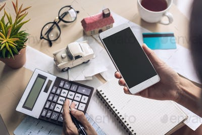 Young woman using smart phone and checking bills