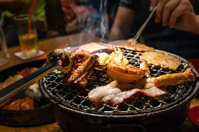 Group of people eating korean barbecue yakiniku in restaurant