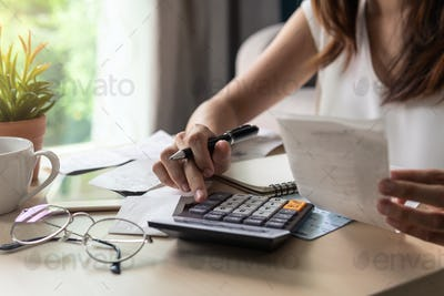 Stressed young woman checking bills in the living room at home