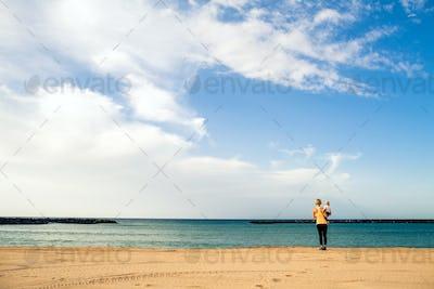 Mother with baby boy enjoying sunrise on a beach