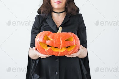 Close up of gothic woman in halloween style clothes with pumpkin in hands