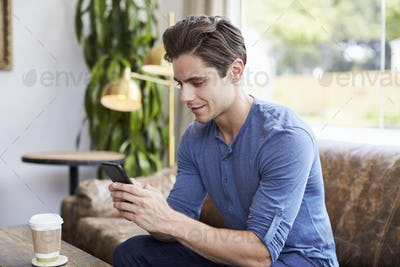 Young Caucasian man using smartphone in a coffee shop