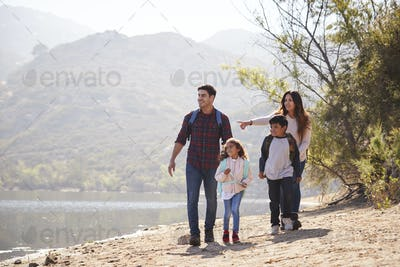 Parents and children hiking together by a lake