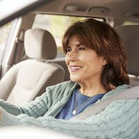 Senior woman in car driving seat looking ahead, close up
