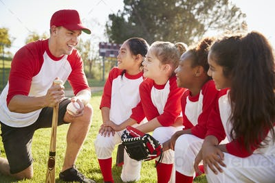Girl baseball team kneeling in a huddle with their coach