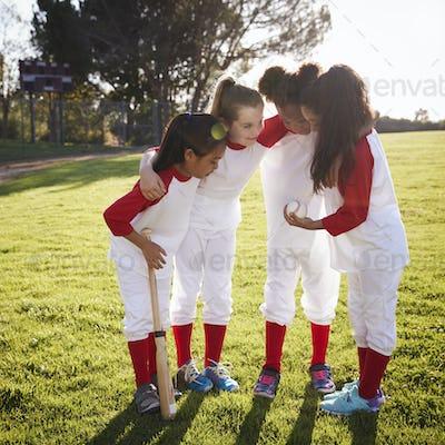 Girl baseball team in a team huddle, motivating before game