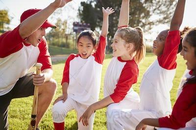 Girl baseball team kneeling with their coach, raising hands
