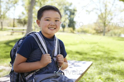 Young Asian schoolboy with backpack smiling to camera
