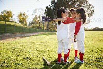 Schoolgirl baseball team talking in team huddle before game