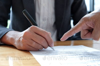 People hand pointing to sign documents.