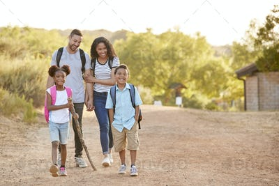 Family Wearing Backpacks Hiking In Countryside Together