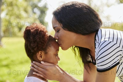 Close Up Of Mother Kissing Daughter In Park
