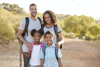 Portrait Of Family Wearing Backpacks Hiking In Countryside Together