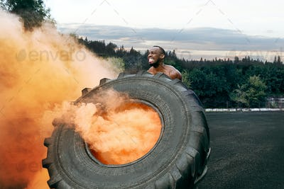 Handsome muscular man flipping big tire outdoor.