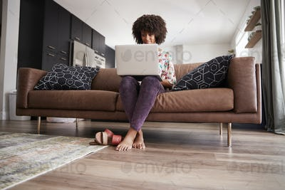 Woman Sitting On Sofa At Home Using Laptop