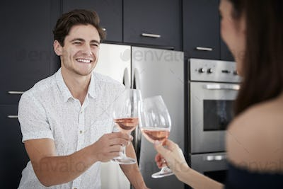 Couple Making Toast As They Drink Wine At Home Standing By Kitchen Island