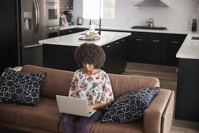 Elevated View Of Woman Sitting On Sofa At Home Using Laptop