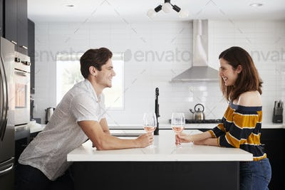 Couple Making Drinking Wine At Home Standing By Kitchen Island