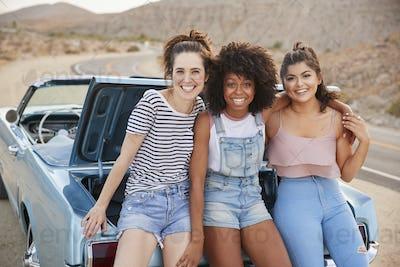 Portrait Of Three Female Friends Sitting In Trunk Of Classic Car On Road Trip