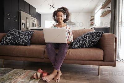 Woman Wearing Wireless Headphones Sitting On Sofa At Home Using Laptop
