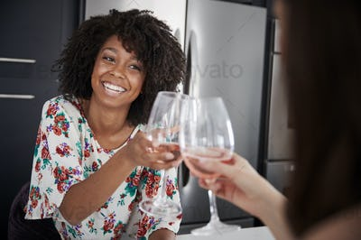 Two Female Friends Making Toast As They Drink Wine At Home Standing By Kitchen Island