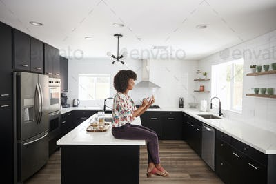 Woman At Home Sitting On Kitchen Island Whilst Using Mobile Phone