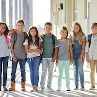 Elementary school kids stand in corridor looking at camera