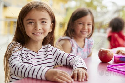 Two young schoolgirls at lunch looking to camera