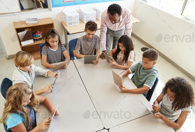 Teacher helping kids using tablets in lesson, elevated view