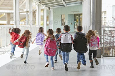 Elementary school kids run from camera in corridor, close up