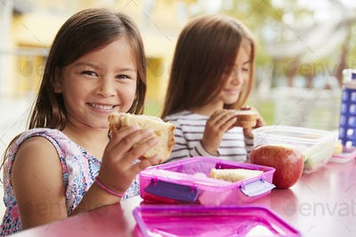 Young schoolgirls holding sandwiches at school lunch table
