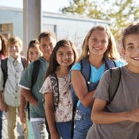 Elementary school kids with backpacks smiling to the camera
