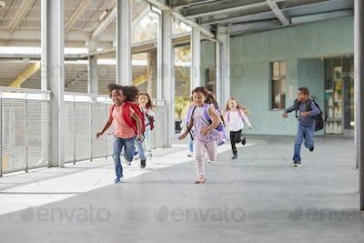 Elementary school kids running in school corridor, side view