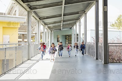 Young school kids running on a walkway in their school