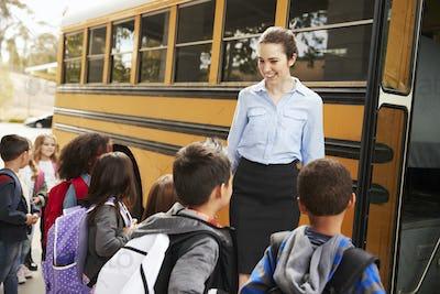 School teacher preparing kids to get on the school bus