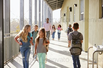 Male teacher and  pupils walking on school campus