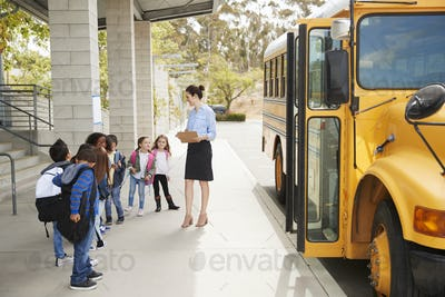 Teacher talks to young school kids by school bus, side view