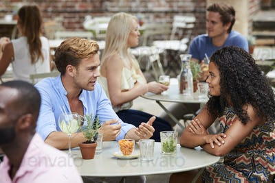 Couple Sitting At Table In Pub Garden Enjoying Drink Together