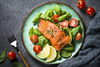 Baked salmon fish fillet with fresh salad top view
