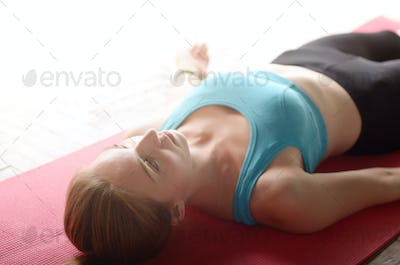 Young Caucasian woman laying in relaxing yoga pose on a mat in t