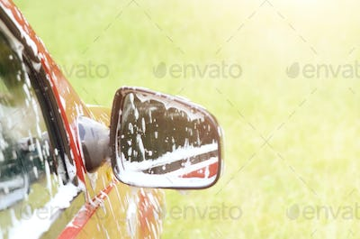 Soap foam on the car window and mirror. Car wash service concept