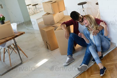 Young happy couple moving in new home and unpacking boxes