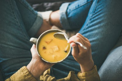 Female keeping mug of warming pumpkin yellow cream soup