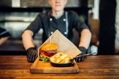 Chef in gloves against juicy burger with steak