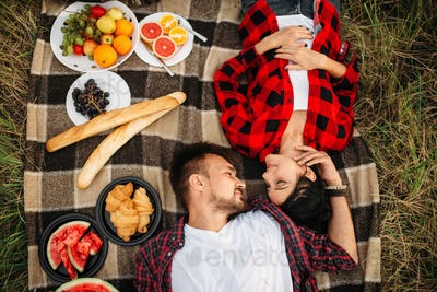 Love couple lies on plaid, top view