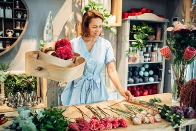 Florist decorates composition with birch bark